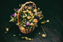 Basket With Yellow And Purple Dried Flowers. Bouquet Of Wilted Roses On A Black Wooden Background. Dried Yellow And Blue Flowers In Autumn Composition.