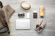Male clothes and accessories with photo camera, mobile phone, laptop and travel objects on wooden background