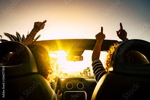 People happy for travel vacation with convertible car giving up hands and dancing for the sea summer holiday vacation - sun on the horizon and joyful concept for free women friends together - 266277855