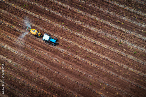 Foto  Aerial view of tractor spraying vineyard with fungicide.