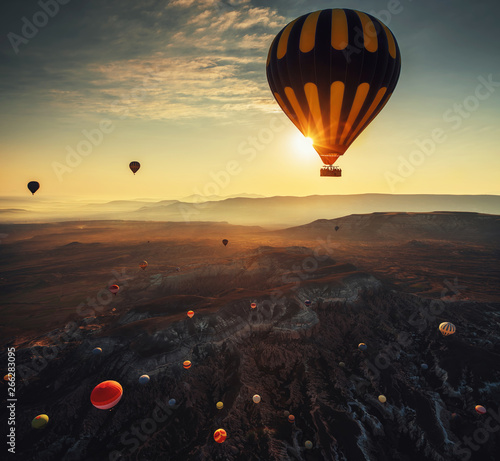 Poster Montgolfière / Dirigeable Hot air balloons flying on sunrise over the valley at Cappadocia. Turkey
