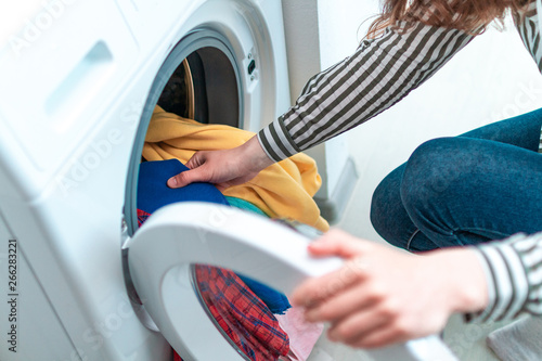 Fotografia, Obraz Loading colored clothes and linen in washing machine