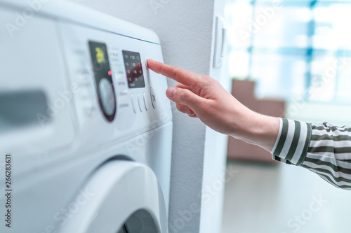 Housewife using display and button for turning on and choosing cycle program on washing machine for laundry at home Canvas Print