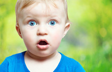 Happy Surprised Toddler With His Blue Eyes And Mouth Open Isolated. Closeup Portrait Of Child Boy Wearing Blue Shirt  On Blur Green Bckground