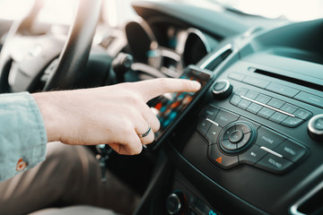 Close up of Caucasian man turning on navigation on smart phone while sitting in his car.