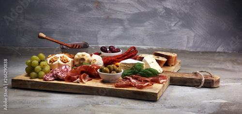 Fotografiet Cutting board with prosciutto, salami, cheese,bread and olives on dark stone bac