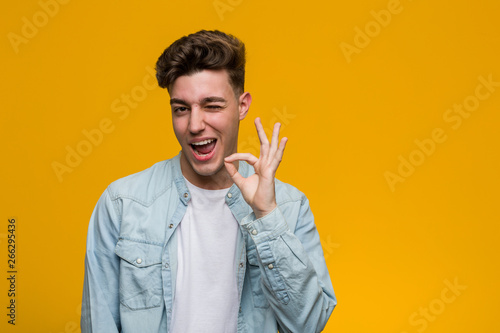 Photographie  Young handsome student wearing a denim shirt winks an eye and holds an okay gesture with hand