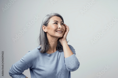 Fotografia  Side profile of charming asian woman smiling on white background