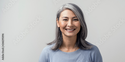 Obraz Beautiful asian with grey hair smiling standing near the wall - fototapety do salonu