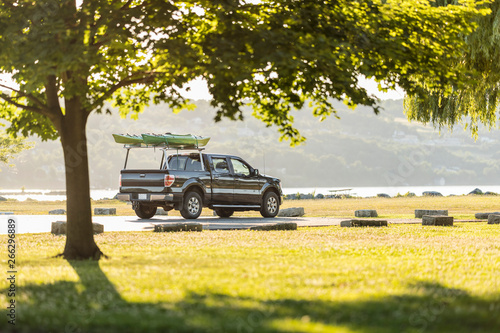 Fotografiet  kayaks and car at lake in a sunny day