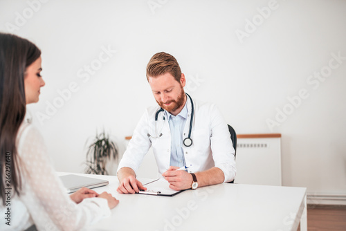obraz PCV Doctor writing application form while consulting female patient in the office.