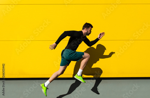 obraz lub plakat Portrait of male athlete running isolated on yellow wall.