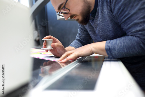 Obraz The printer at the stage watches the print quality through a magnifying glass. - fototapety do salonu