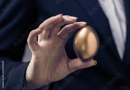 Tablou Canvas golden egg in female hand