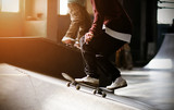 A fashionably dressed guy rides a skateboard on a ramp illuminated by sunlight, and is going to make a jump, and against the background of another skater does a trick with a slip