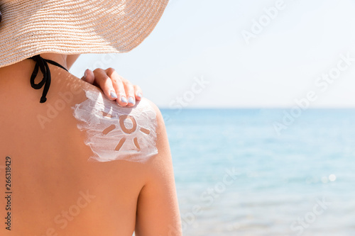 Photo  Sunscreen lotion in sun shape on tanned woman's shoulder