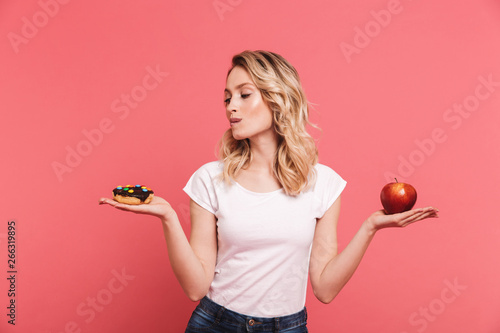 Photo  Portrait of hesitating blond woman 20s wearing casual t-shirt holding sweet donu