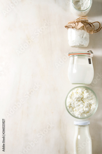 Set of farm dairy produce cottage cheese, milk cream, plain yogurt in reusable eco friendly glass jars and bottle in row over white marble background. Flat lay, space