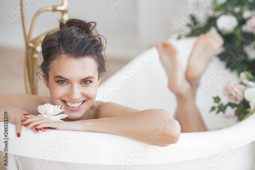 Valokuvatapetti Perfact woman bathing with flowers and milk