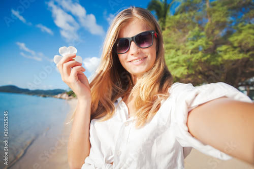 Valokuva  young happy blonde beautiful girl on tropical sea  background, smiling happy gir