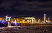 Touristic Landmark In Saint Petersburg, Russia: The Spit Of Vasilievsky Island Illuminated By Winter Night With The Historical Exchange Building, The Rostral Columns, Lanterns And Granite Embankment