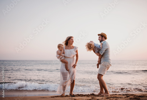 A young family with two toddler children having fun on beach on summer holiday. - 266328030