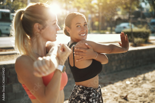 Two fit women smiling and stretching before an outdoor run