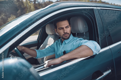 Enjoying car ride. Handsome young man in smart casual wear looking away while driving a status car - 266335272