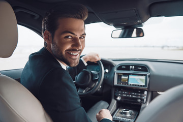 Ready to go! Handsome young man in full suit looking at camera and smiling while driving a car