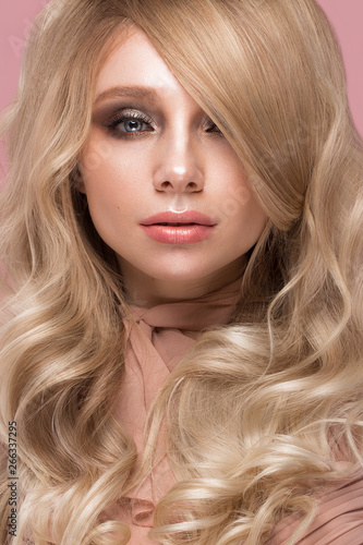 Valokuva  Beautiful blond girl with curls hair, looks like a doll, with glamorous make-up in pink clothes
