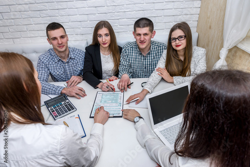 Group of young consultants in office pointing at 1040 tax form Wallpaper Mural