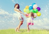 Beautiful happy mother with daughter having fun in green field holding colorful balloons