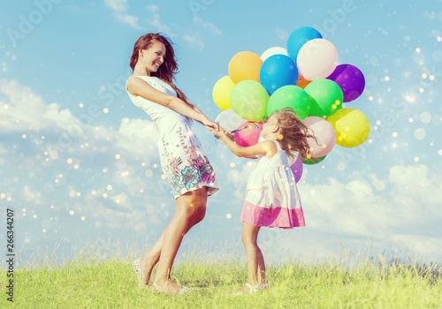 Poster de jardin Individuel Beautiful happy mother with daughter having fun in green field holding colorful balloons