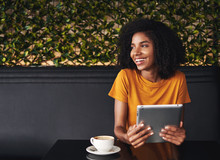 Happy Young Woman Sitting In Cafe Holding Digital Tablet In Hand