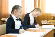 The Schoolgirl Did Not Learn The Subject Of The Lesson At School And Looks Into Someone Else's Notebook To Write Off The Correct Answer Girl Classmate Looks Into Someone Else's Notebook.
