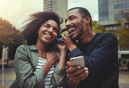 Young couple listening music on one headphone - 266351246