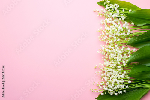 Photo Stands Lily of the valley Floral background with lily of the valley flowers. Flat lay, top view, pastel pink background, copy space. Lovely greeting card with lily of the valley for Mothers day, wedding or birthday.