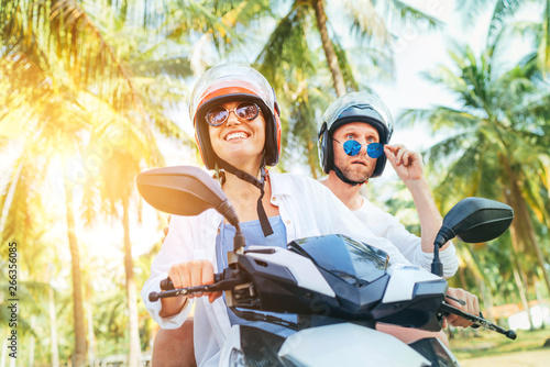 Fototapeta Сouple travelers riding motorbike scooter in safety helmets during tropical vacation under palm trees obraz na płótnie