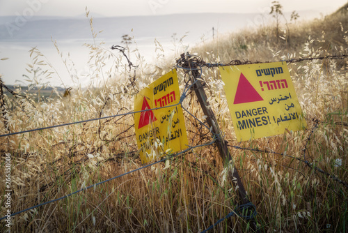 Fotografie, Obraz  Yellow warning sign next to a mine field, close to the border with Syria, in the Golan Heights, Israel