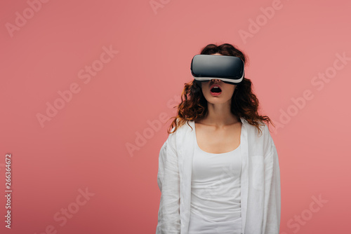Cadres-photo bureau Kiev surprised curly young woman wearing virtual reality headset on pink