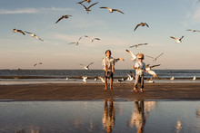 Two Siblings Playing With Birds On Galveston Island