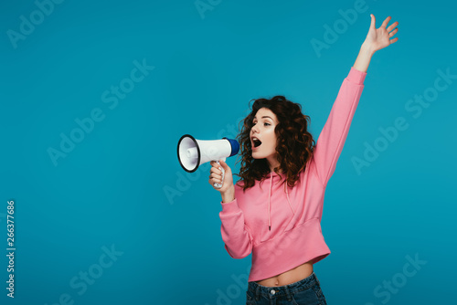 Fotografija attractive curly redhead girl screaming in megaphone on blue