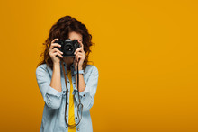 Curly Redhead Photographer Covering Face With Digital Camera Isolated On Orange
