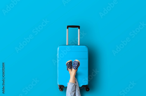 Blue suitcase on the blue background Fotobehang
