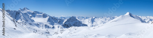 Fototapeta Panoramic landscape view from top of Schaufelspitze on winter landscape with snow covered mountain slopes and pistes at Stubai Gletscher ski resort at spring sunny day. Blue sky background. Stubaital obraz