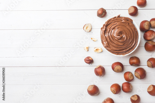 Obraz na plátně  Nougat nut chocolate in a plate on a white background with hazelnut nuts