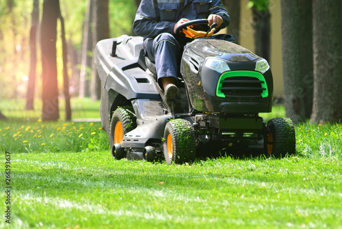 Montage in der Fensternische Lime grun Professional lawn mower with worker cut the grass in a garden