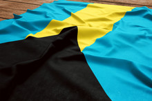 Flag Of Bahamas On A Wooden Desk Background. Silk Bahamian Flag Top View.