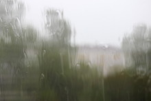 Water Flows Down The Wet Glass On The Background Of Blurred Trees And Houses - Autumn Rainy Urban Landscape, Texture For Backdrop