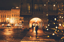 Night Street In A European City With Bokeh From Christmas Lanterns, Silhouettes Of People And Facades Of Buildings In The Old Town. Christmas Travel Concept